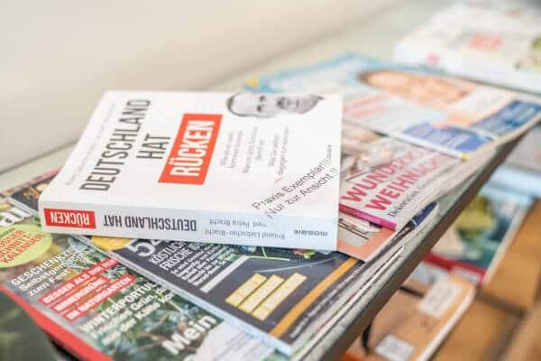 Ablage von verschiedenen Zeitschriften und oben drauf das Buch: Deutschland hat Rücken.