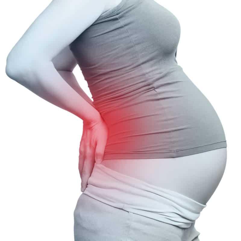 Schwangere fasst sich an rot markierten Rücken