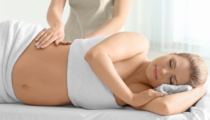 Schwangere Frau liegt auf einer Massageliege und wird von einem Masseur behandelt