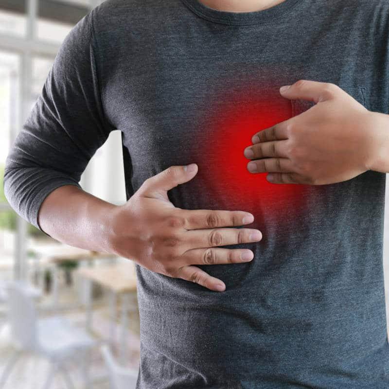 Mann hält sich einen rot eingefärbten Bereich hinter der Brust