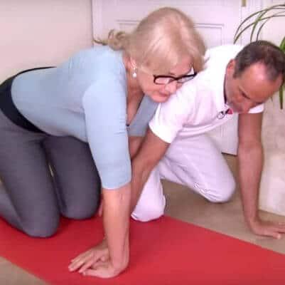 Roland Liebscher-Bracht zeigt einer Patientin eine Dehn- und Kräftigungsübung bei Hypermobilität des Handgelenks. Die Patientin kniet auf einer roten Übungsmatte und dehnt ihr rechtes Handgelenk maximal, indem die Finger der rechten Hand bei durchgestrecktem Ellenbogen auf dem Boden liegend zum rechten Knie zeigen.