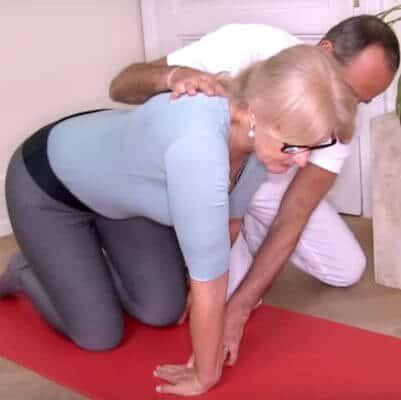 Roland Liebscher-Bracht zeigt einer Patientin eine Dehn- und Kräftigungsübung bei Hypermobilität des Handgelenks. Die Patientin kniet auf einer roten Übungsmatte und dehnt ihr rechtes Handgelenk, indem die Finger der rechten Hand bei durchgestrecktem Ellenbogen auf dem Boden liegend zum rechten Knie zeigen. Der Dehnungswinkel des Handgelenks ist dabei nicht maximal, da die Patientin ihren Oberkörper leicht nach vorne nimmt.