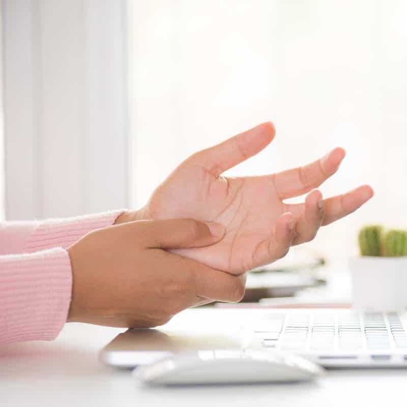 Frau reibt mit dem Daumen über die schmerzende Handinnenfläche bei Handschmerzen.