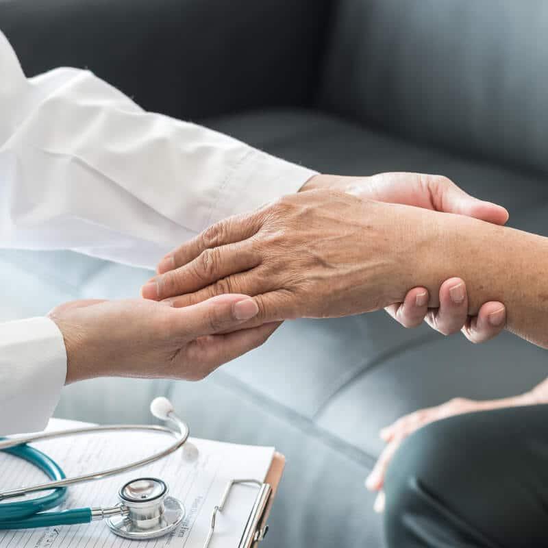 Ein Arzt untersucht das Handgelenk eines Patienten, der auf einer Couch sitzt