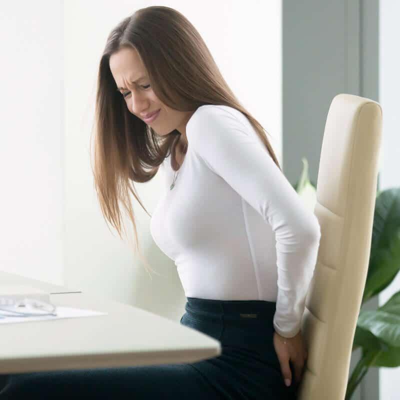 Eine Frau sitzt in ihrem Büro am Schreibtisch und fässt sich mit schmerzverzerrtem Gesicht an das Gesäß