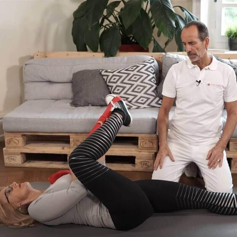 Eine Frau macht eine Dehnungsübung gegen Gesäßschmerzen, indem sie auf dem Rücken liegend ihren rechten Fuß mit einer Übungsschlaufe in Richtung ihrer linken Schulter zieht