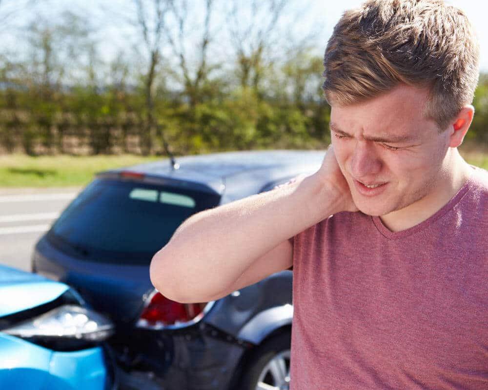 Ein junger Mann hält sich seinen schmerzenden Nacken, im Hintergrund sind zwei Autos nach einem Auffahrunfall zu sehen