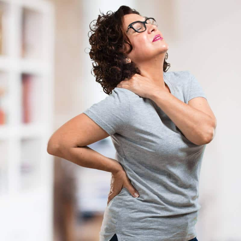 Eine Frau steht in ihrer Wohnung und hält sich mit der linken Hand ihre aufgrund eines HWS-Syndroms schmerzende rechte Nackenseite