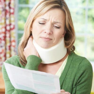 Frau mit Halskrause schaut schmerzverzerrt auf ihr Diagnoseblatt und hält sich mit einer Hand ihren Hals