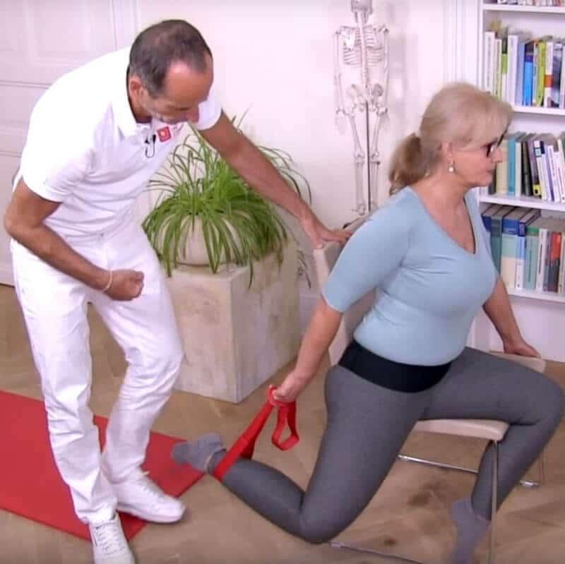 Patientin führt Übung gegen Patellasehnen-Schmerzen aus. Dabei sitzt sie auf einer Stuhlkante mit der linken Gesäßhälfte und führt das andere Beine mit der Übungsschlaufe nach hinten. Das Knie ist dabei abgewinkelt.