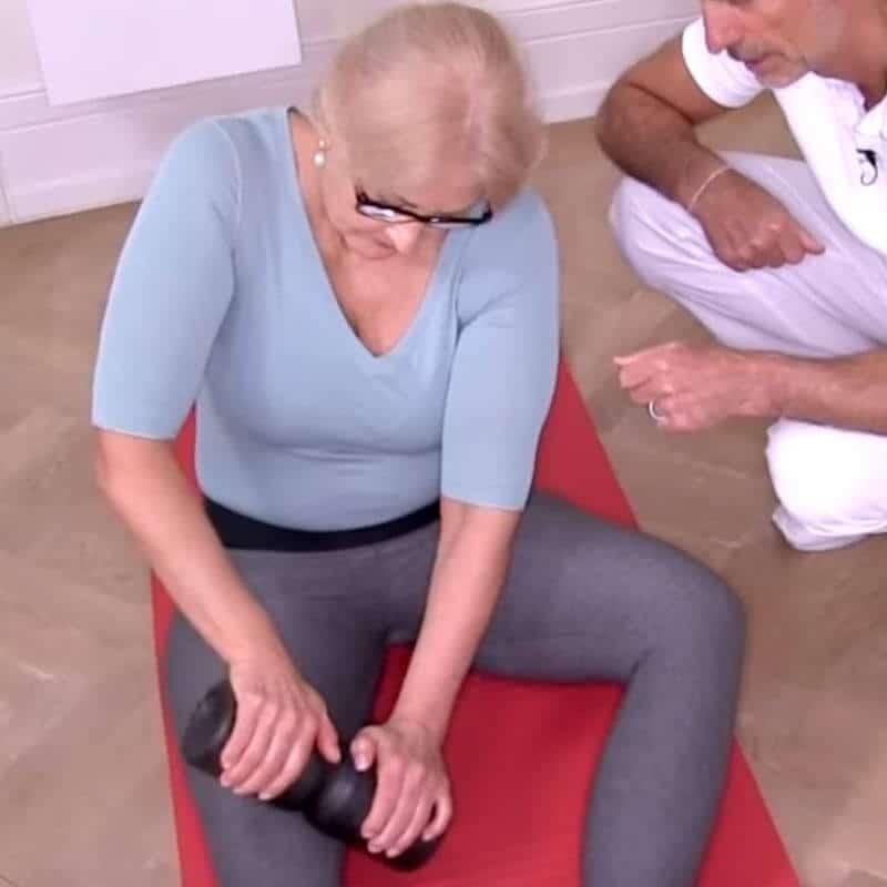 Patientin führt mit der Medi-Rolle die Faszien-Rollmassage gegen Patellasehnen-Schmerzen am Oberschenkel aus