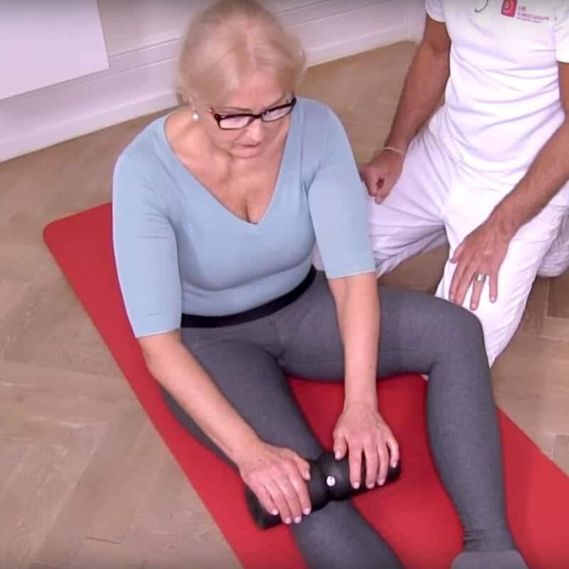 Patientin sitzt mit ausgestreckten Beinen auf dem Boden. Sie hält mit beiden Händen die Medi-Rolle und rollt sie von der Kniescheibe über ihren Oberschenkel.