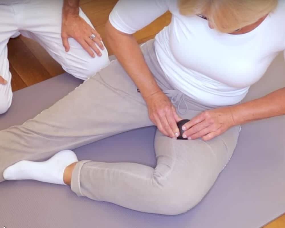 Patientin massiert ihren inneren Oberschenkel bzw. ihre Leiste gegen Piriformis-Syndrom