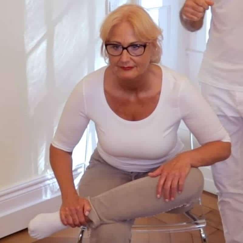 Patientin sitzt auf einem Stuhl mit dem linken Unterschenkel über das rechte Knie gelegt. Der Oberkörper ist nach vorne gebeugt, um die Dehnung im Gesäß bzw. dem Piriformis Muskel zu spüren.