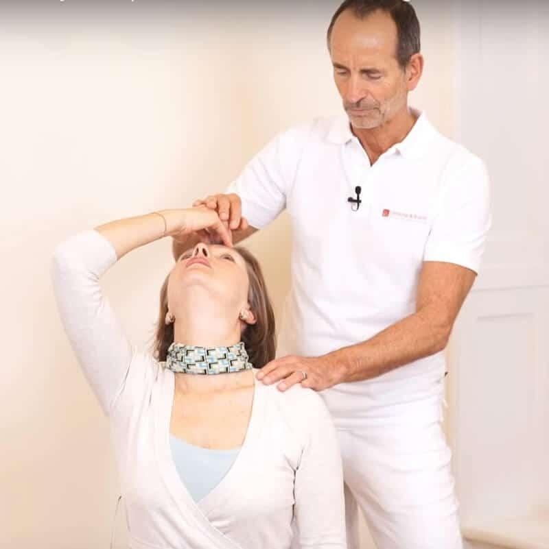 Schmerzspezialist Roland Liebscher-Bracht zeigt einer Patientin eine Dehnübung gegen das HWS-Syndrom: Die Patientin sitzt auf einem Stuhl und überstreckt ihren Kopf gerade nach hinten, wobei eine Hand auf der Stirn zur Unterstützung dient.