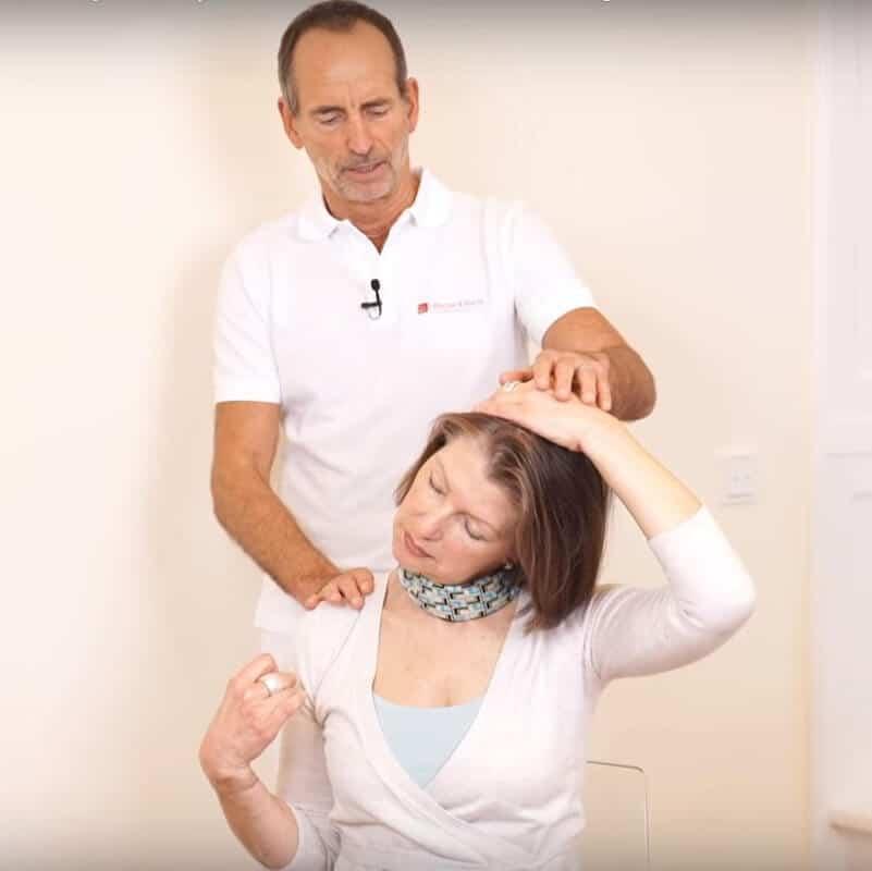 Schmerzspezialist Roland Liebscher-Bracht zeigt einer Patientin eine Dehnübung gegen das HWS-Syndrom: Die rechte Faust ist geballt, der rechte Arm gebeugt, die Patienten schaut sitzend 45 Grad nach rechts und zieht ihren Kopf mithilfe der linken Hand nach links.