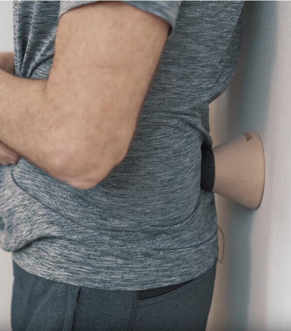Roland lehnt sich gegen den Drücker an der Wand bei Rückenschmerzen