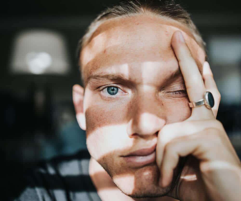 Mann stützt sein Gesicht auf eine Hand und verzieht dabei das Gesicht mit Gesichtsschmerzen.