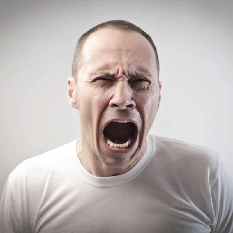 Mann reißt den Mund weit auf und kneift die Augen zusammen bei Gesichtsschmerzen