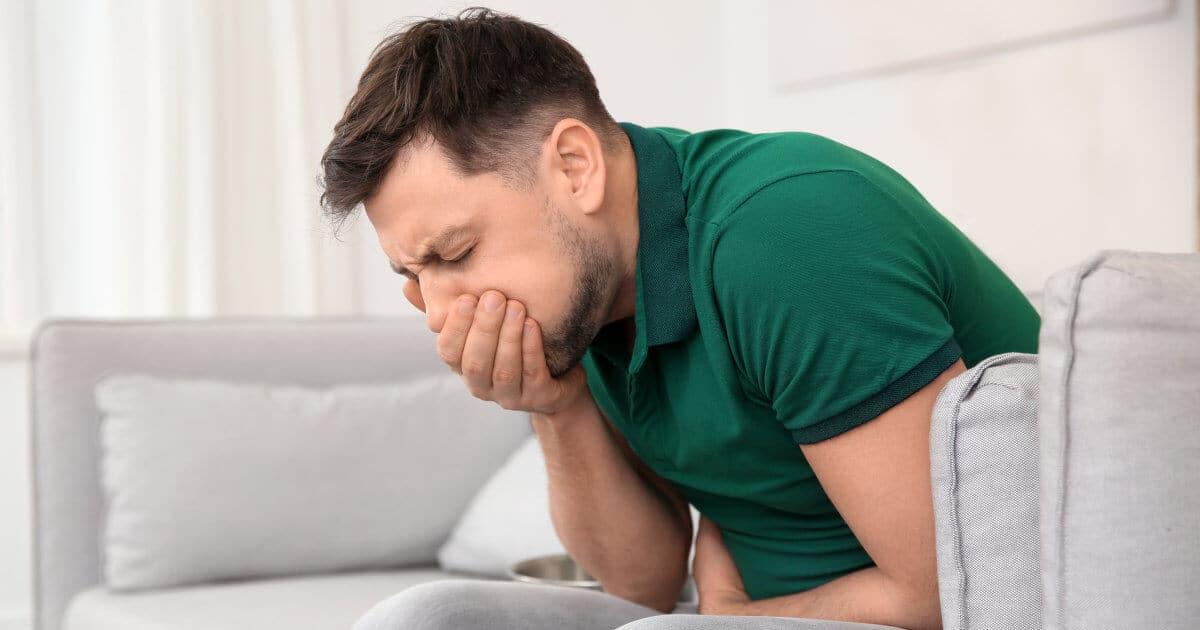 Mann hält sich die Hand vor seinen Mund und beugt sich krampfhaft zusammen, weil ihm übel ist