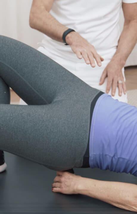 Eine Frau liegt in Rückenlage auf einer Matte und hält sich den Drücker in ihren Gesäßbereich, um die Light-Osteopressur anzuwenden