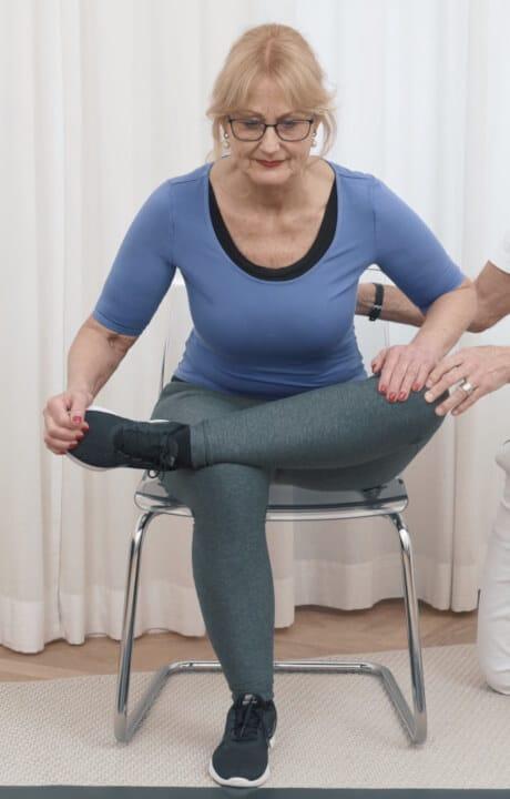 Eine Frau sitzt auf einem Stuhl und hat ihr linkes Bein über das recht im 90-Grad-Winkel abgelegt. Sie zieht sich mit ihren Händen nun im Hohlkreuz nach vorn.