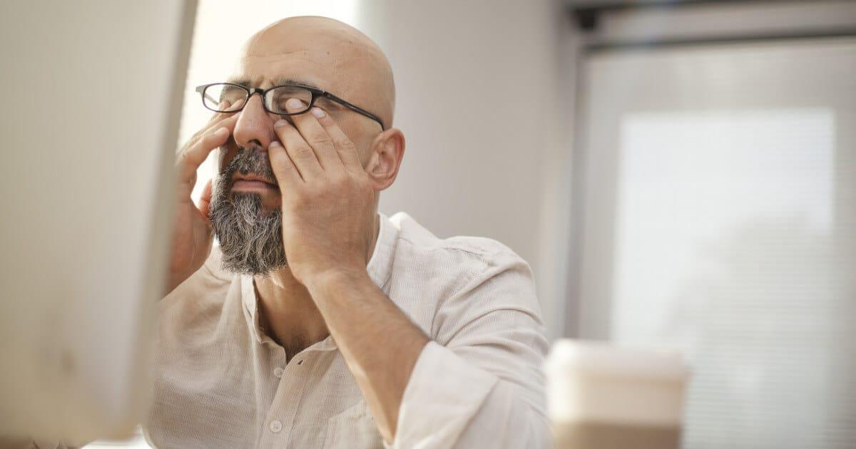 Mann mit Brille vor dem PC Bildschirm reibt sich die Augen aufgrund von Augenschmerzen