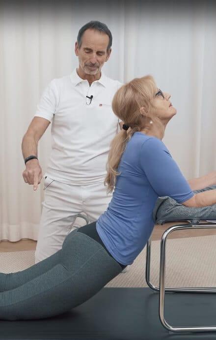 Angeleitet von Schmerzspezialist Roland Liebscher-Bracht führt eine Patientin eine Dehnübung gegen LWS-Schmerzen aus, indem sie ihre Arme auf einem Stuhl ablegt und die Hüfte durchhängen lässt
