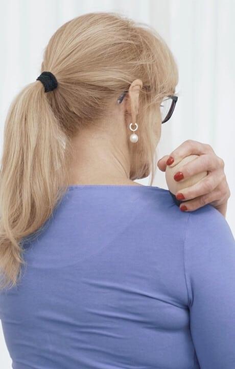 Frau drückt mit dem Drücker auf einen Schmerzpunkt am Schulterblatt