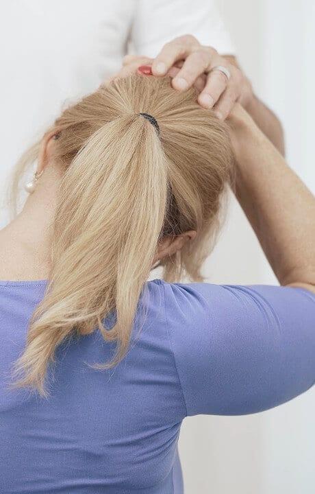 Frau dehnt ihren Kopf auf die rechte Seite, um Nackenschmerzen zu lindern