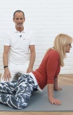 Frau streckt auf allen Vieren ihren Oberkörper nach oben und winkelt dabei ihr rechtes Bein seitlich an, um ihre Schambeinentzündung zu lösen