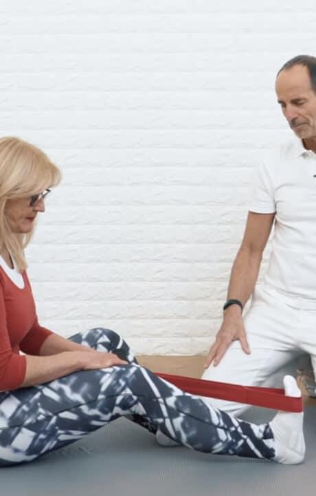Eine Frau zieht mithilfe einer Übungs-Schlaufe ihren Fuß nach hinten, um ihren Wadenkrampf zu lösen.