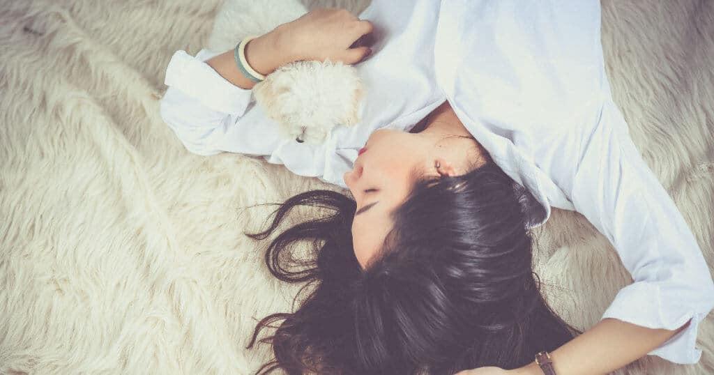 Eine Frau liegt auf einer Decke auf dem Rücken und schläft. Ihr rechter Arm ist nach oben gestreckt und mit dem linken Arm umarmt sie einen kleinen Hund.