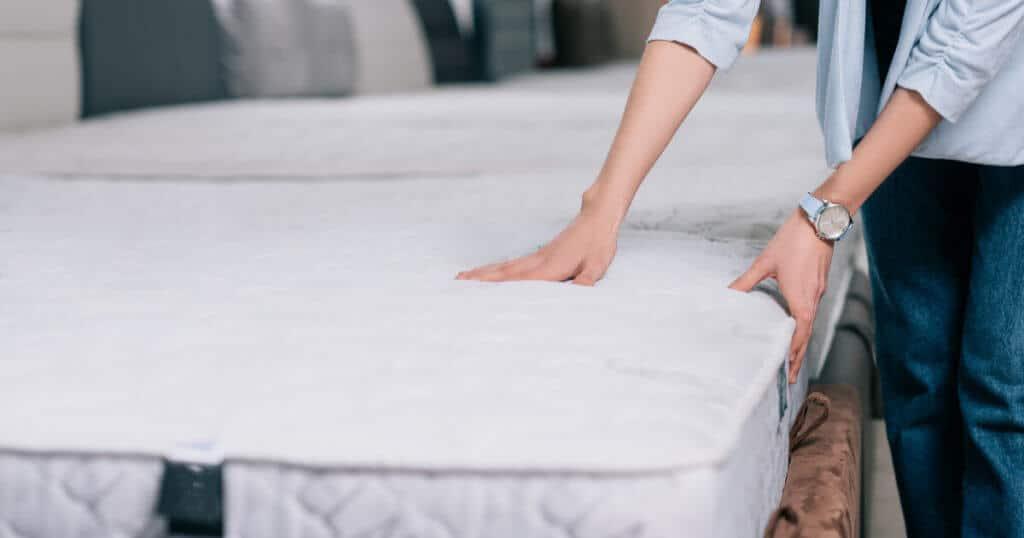Eine Frau betastet eine unbezogene Matratze im Geschäft, um die Härte zu testen.