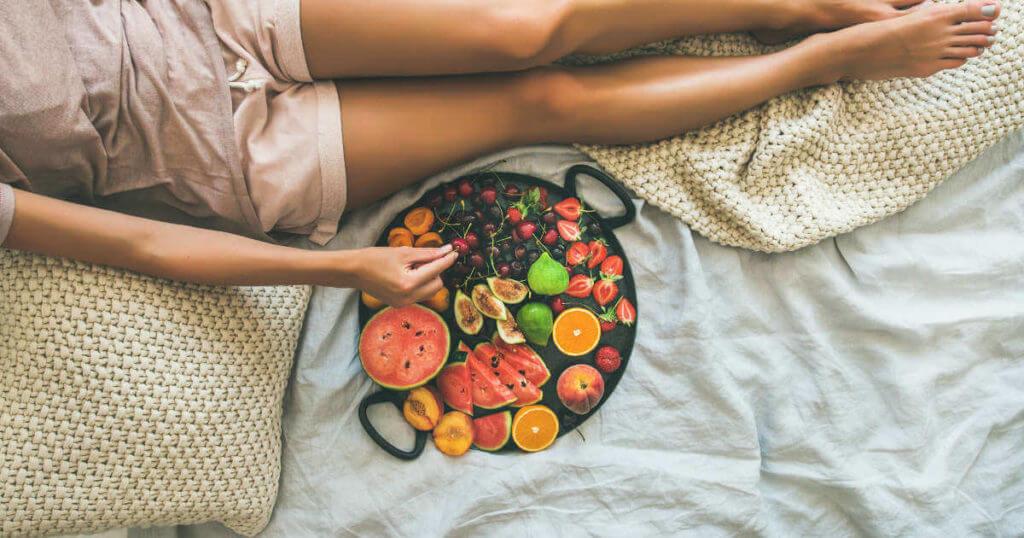 Eine Frau liegt auf dem Bett und greift zu einer Obst-Platte, die neben ihr liegt.