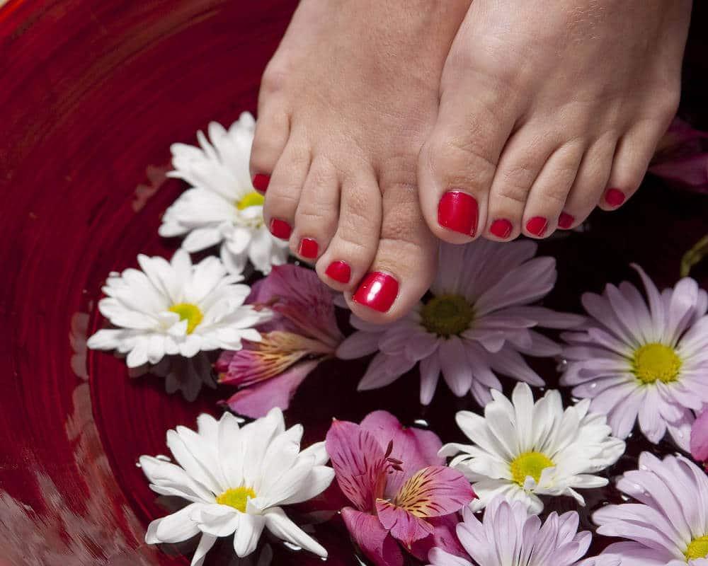 Zu sehen sind Füße über einem Fußbad mit Blumen und einem leicht ausgeprägten Hallux valgus.