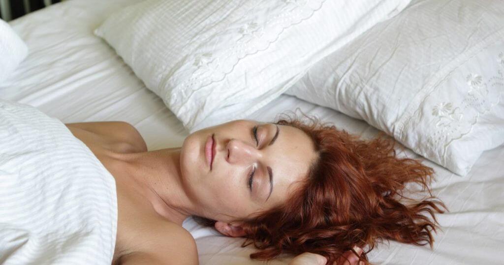 Eine Frau liegt im Bett auf dem Rücken. Sie hat die Decke bis zu ihrem Oberkörper hochgezogen und ihr Kopf liegt direkt auf der Matratze unterhalb ihrer zwei Kissen auf.