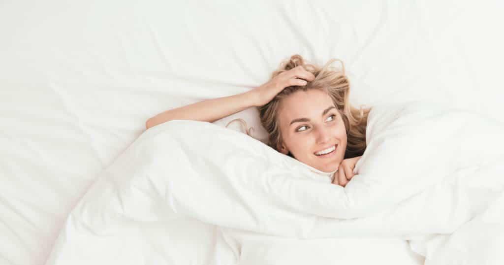 Eine Frau liegt im Bett auf dem Rücken, hat die Decke bis zu ihrem Kinn hochgezogen und greift sich mit der rechten Hand an ihren Kopf. Sie lächelt und schaut zur Seite.