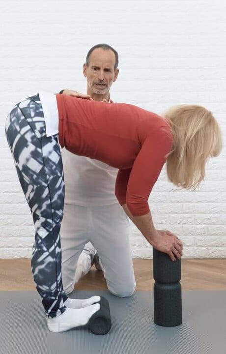 Eine Frau ist mit ihren Fußspitzen auf der Liebscher & Bracht Medi-Rolle und beugt ihren Oberkörper weit nach vorne, sodass die komplette Rückseite ihres Unterkörpers gedehnt wird.