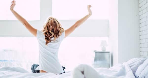 Eine Frau ist ohne Schmerzen aufgewacht, sitzt auf ihrem Bett und streckt sich morgens dem Fenster zugewandt.