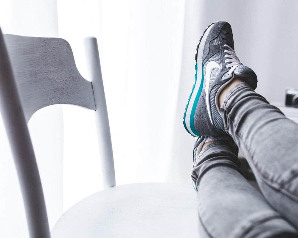 Frau legt die Beine auf einen Stuhl zur Schonung bei einer Plantarfasziitis.