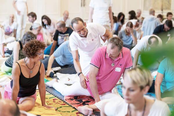 Viele Personen im Raum führen die selbe Übung aus und ein Man wird vom weiß gekleideten Ausbilder korrigiert