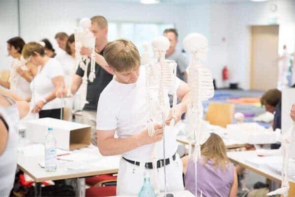 Verschiedene Personen in einem Ausbildungsraume setzen ein künstliches Skelett, jeder für sich selbst, zusammen