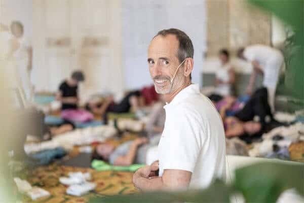 Ein weiß gekleideter sitzender Herr Roland Liebscher Bracht dreht sich um, lächelt in die Kamera. Im Hintergrund liegen Leute