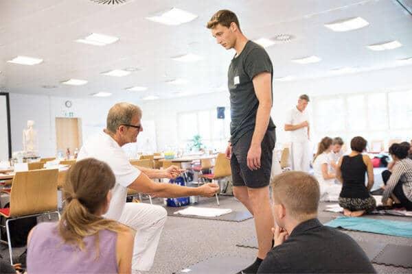 In einem Ausbildungsraum mit mehreren Personen zeigt ein kniender Ausbilder einem sportlichem Mann eine Übung