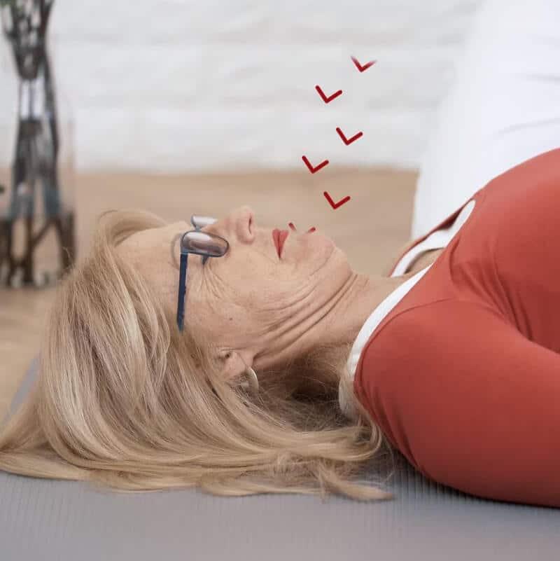 Eine Patientin drückt auf dem Rücken liegend ihr Kinn und den Kehlkopf nach unten, die Krafteinwirkung ist mit roten Pfeilen dargestellt