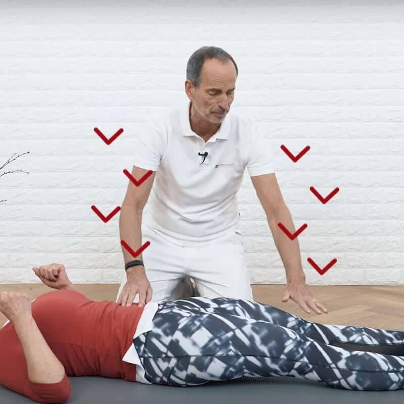 Eine Patientin drückt auf dem Rücken liegend ihre Lendenwirbelsäule und die Knie nach unten, die Krafteinwirkungen sind mit roten Pfeilen dargestellt