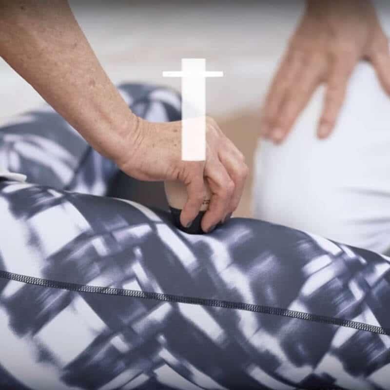 Eine Patientin mit Restless Legs wendet am Oberschenkel eine Light-Osteopressur mit dem Schmerzfrei-Drücker an. Die senkrechte Drückrichtung ist grafisch dargestellt.