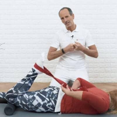 Schmerzspezialist Roland Liebscher-Bracht zeigt einer Patientin eine Dehnübung gegen Restless Legs. Die Patientin liegt auf dem Bauch, ihr Knie liegt auf der Medi-Rolle ab und sie zieht ihren Fuß mithilfe der Übungs-Schlaufe zum Gesäß.