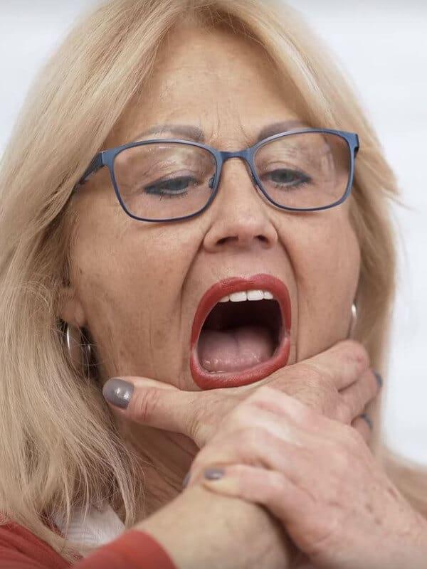 Schmerzspezialist Roland Liebscher-Bracht leitet eine Patientin bei einer Übung gegen Zähneknirschen an. Der Mund ist weit geöffnet und der untere Kiefer wird mithilfe der Hände nach unten gezogen.